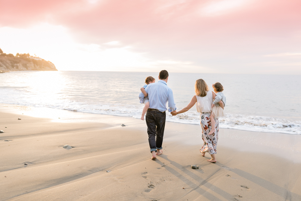 family photography, family walking at the beach with a beautiful pink sunset sky