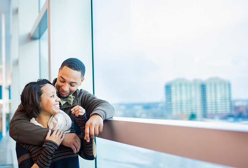 Downtown-Indianapolis-Central-Library-engagement-portrait-photographer-couple-snuggle-in-window-with-skyline-in-background.jpg