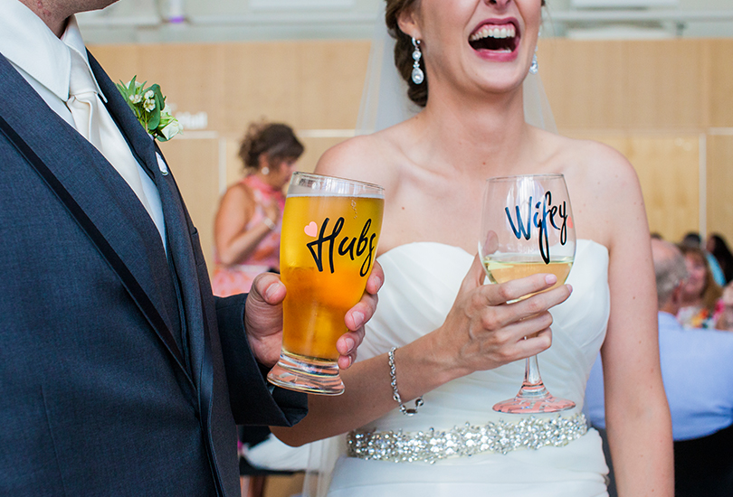 Columbus-Indiana-wedding-photographer-bride-and-groom-holding-custom-glasses-wifey-hubs.jpg