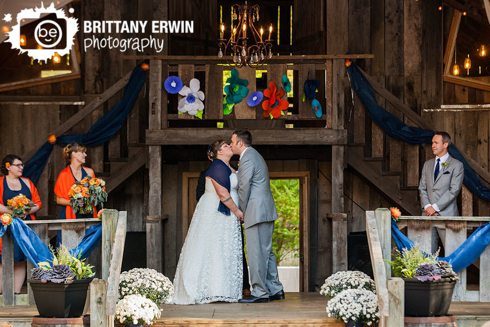 Story-Inn-barn-wedding-ceremony-paper-flower-altar-couple-first-kiss.jpg