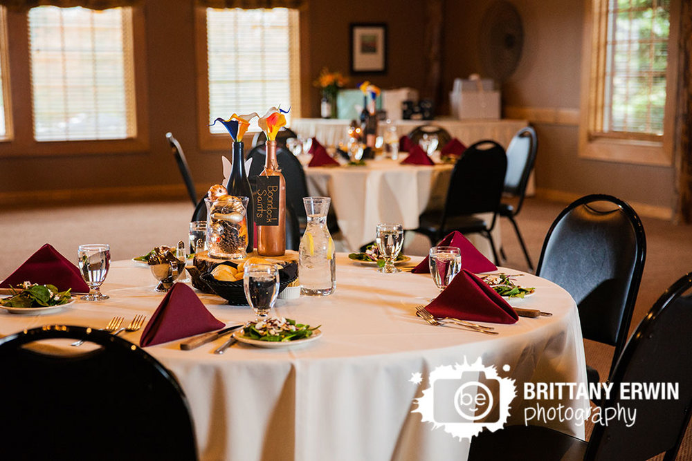 Purgatory-Golf-Club-reception-wedding-photographer-wine-bottle-centerpiece-burgundy-napkin-place-setting.jpg