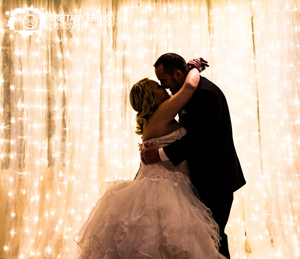 Ricks-cafe-boatyard-wedding-photographer-winter-couple-first-kiss-ceremony-twinkle-light-curtain.jpg