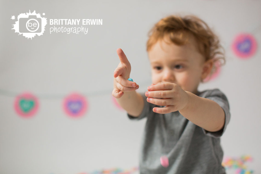 Indianapolis-studio-portrait-photographer-valentines-day-boy-conversation-heart-playing-on-white-backdrop.jpg