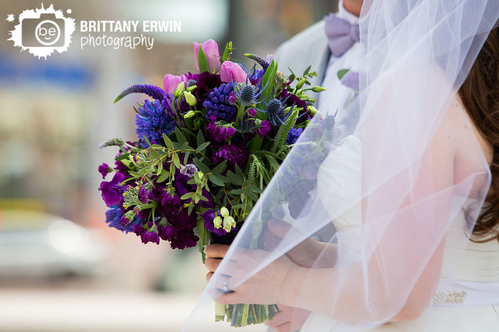 Downtown-Indianapolis-wedding-photographer-bride-holding-violets-are-blue-purple-bouquet-thistle-tulips.jpg