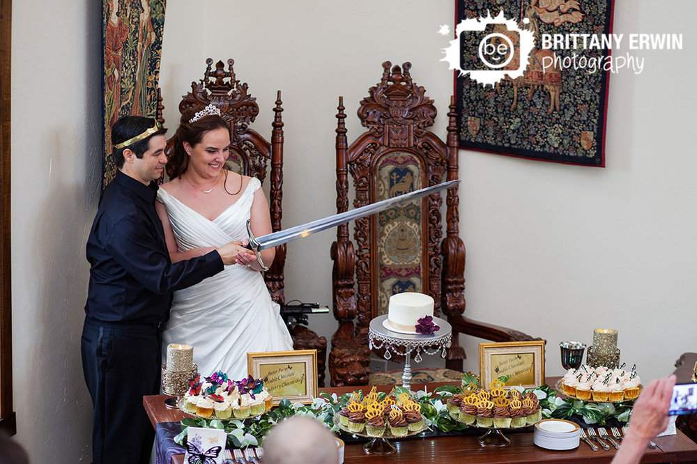 Clayshire-Castle-wedding-photographer-bride-groom-cut-cake-sword-at-dessert-table.jpg