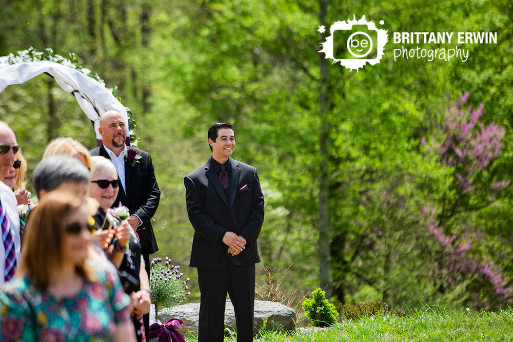 Outdoor-wedding-ceremony-at-Clayshire-Castle-in-Indiana-groom-reaction-seeing-bride-first-time.jpg