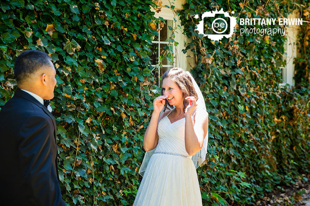 First-look-bride-reaction-teary-eyes-by-ivy-covered-wall.jpg