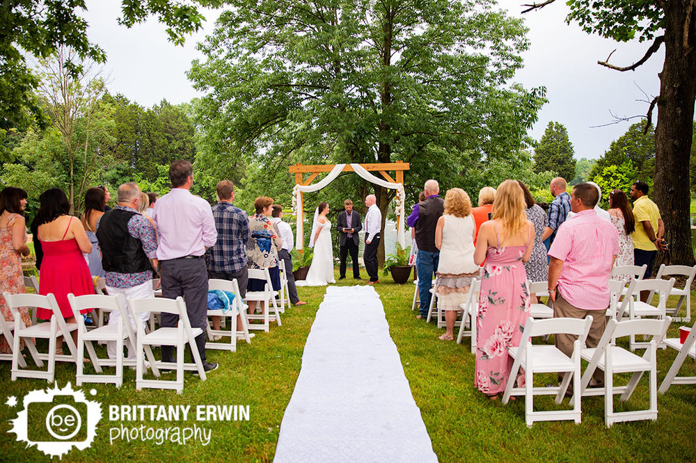 Ceremony-wedding-photographer-couple-at-altar-wooden-arbor-aisle-runner.jpg