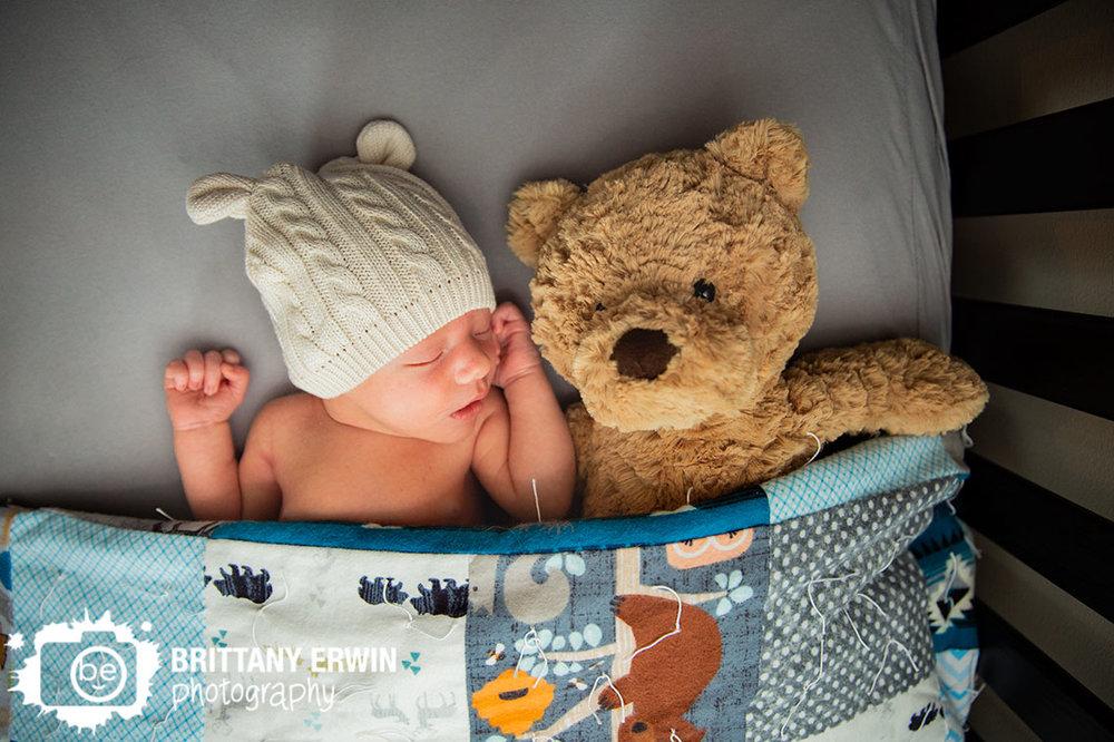 sleepy-baby-boy-in-crib-tucked-in-with-teddy-bear.jpg