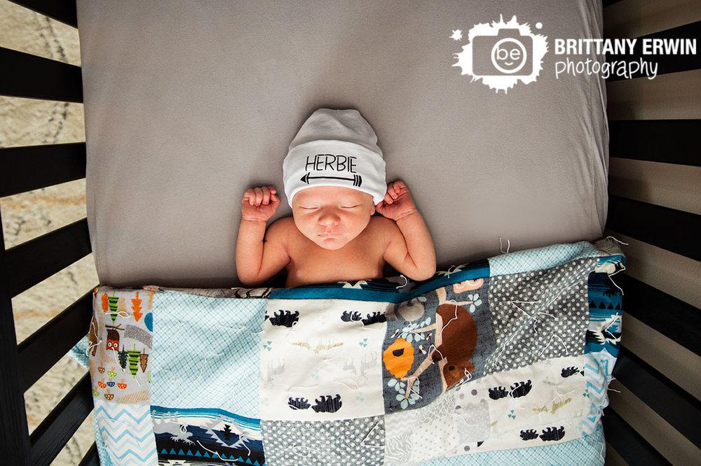 Indianapolis-newborn-lifestyle-portrait-photographer-baby-boy-asleep-tucked-in-crib-custom-hat.jpg