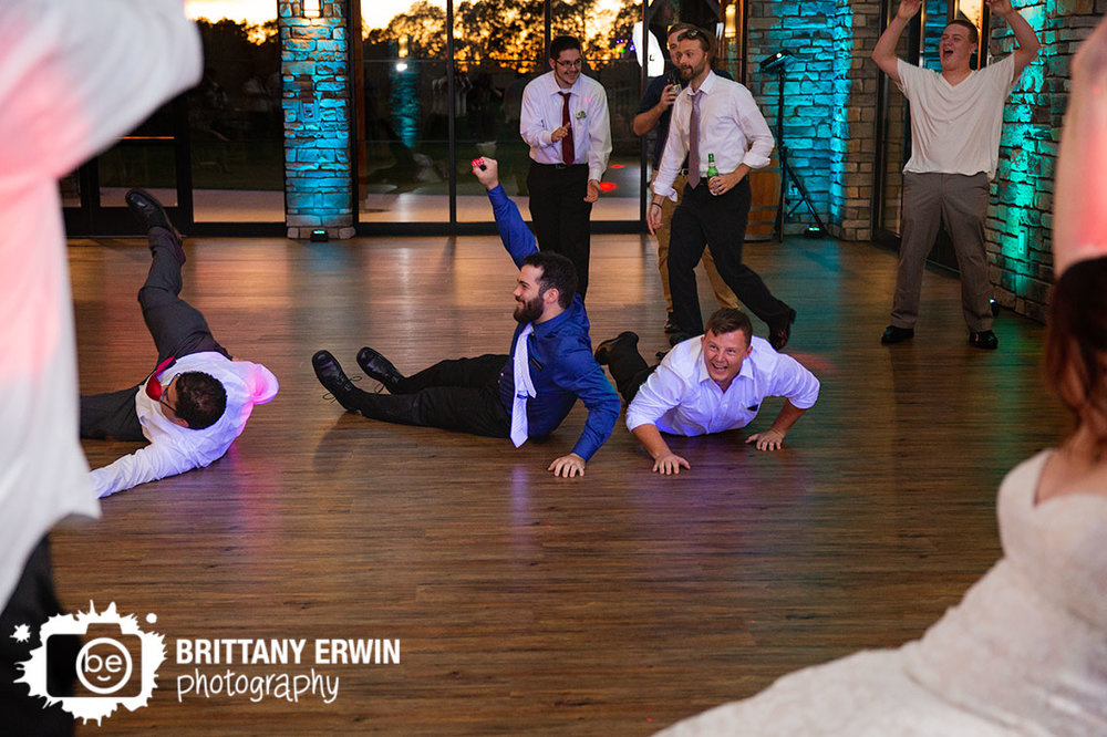 Sycamore-at-Mallow-Run-wedding-photographer-reception-garter-toss-guys-dive-on-floor.jpg