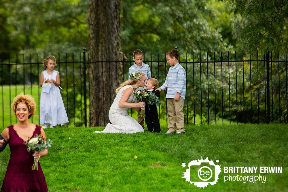 Wedding-photographer-garfield-park-bride-give-kiss-to-son-ring-bearer-at-back-of-ceremony.jpg