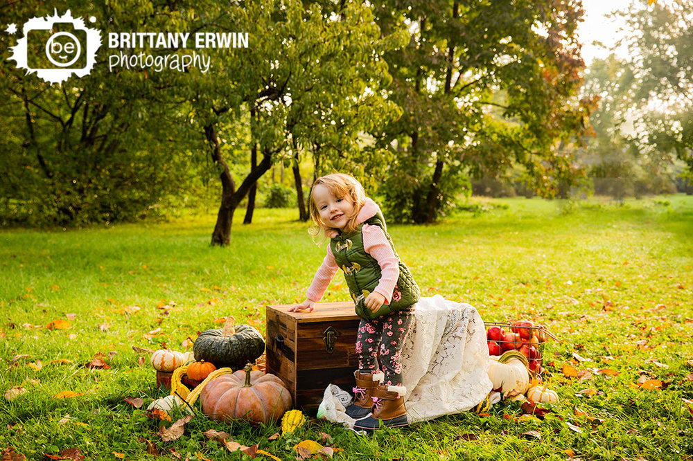 Indianapolis-fall-mini-session-little-girl-vest-pink-shirt-pumpkin-apples.jpg