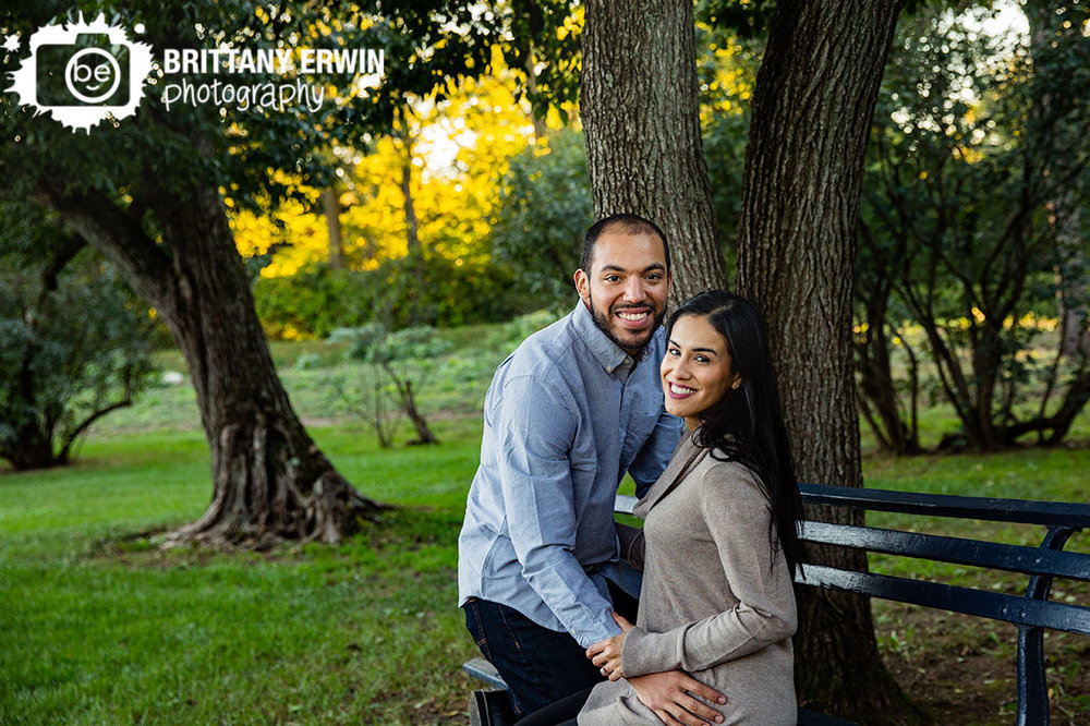 Indianapolis-fall-engagement-portrait-photographer-couple-on-bench-under-trees-holcomb-gardens.jpg