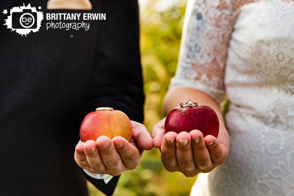 Wea-Creek-Orchard-wedding-photographer-apple-rings-on-fruit-couple-holding-apples.jpg