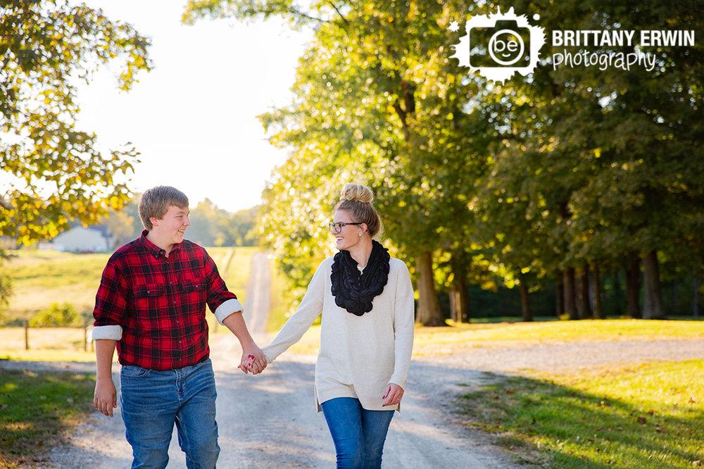 Engagement-portrait-photographer-couple-walking-down-long-driveway-gravel-path-sunset-fall.jpg