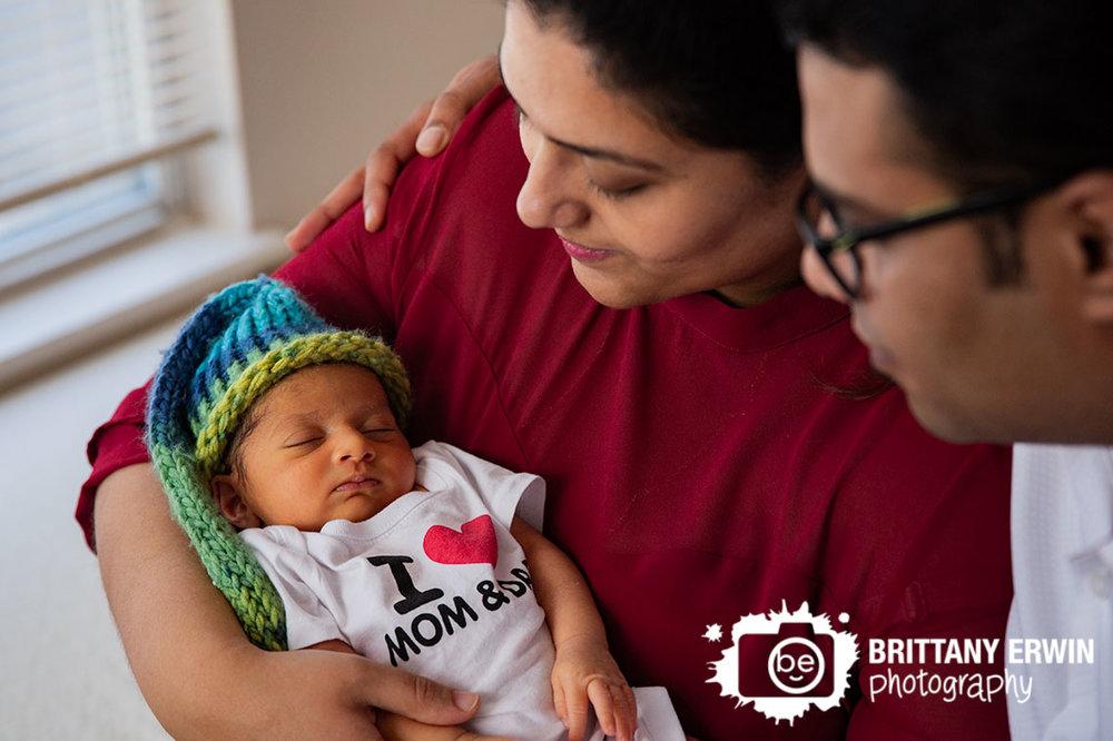 Indianapolis-lifestyle-newborn-photographer-mom-dad-holding-baby-boy-heart-onesie.jpg