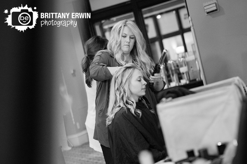 Indianapolis-wedding-photo-bride-getting-hair-curled-by-stylist-in-mirror.jpg