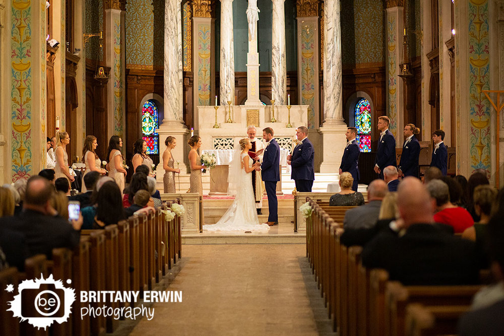 Catholic-church-historic-building-wedding-ceremony-couple-at-altar-holding-hands-with-bridal-party.jpg
