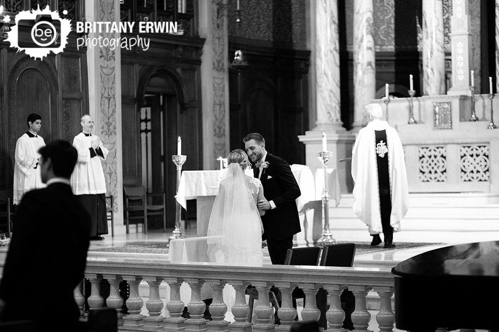 Saint-Joan-of-Arc-wedding-ceremony-groom-smiling-at-bride-catholic-sign-of-peace.jpg