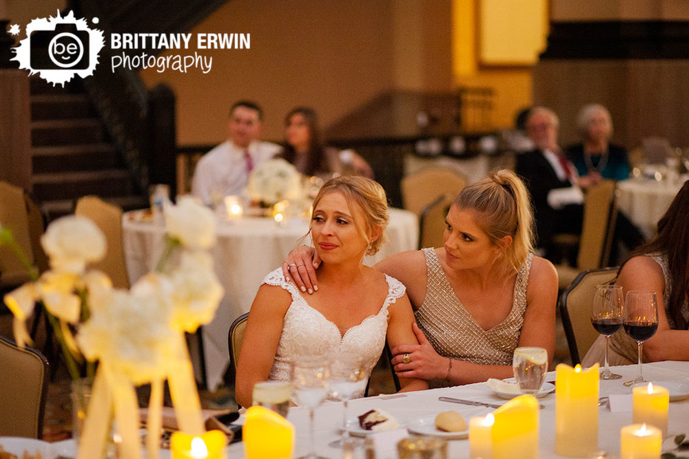 Indianapolis-wedding-reception-photographer-bride-reaction-sitting-with-bridesmaid.jpg