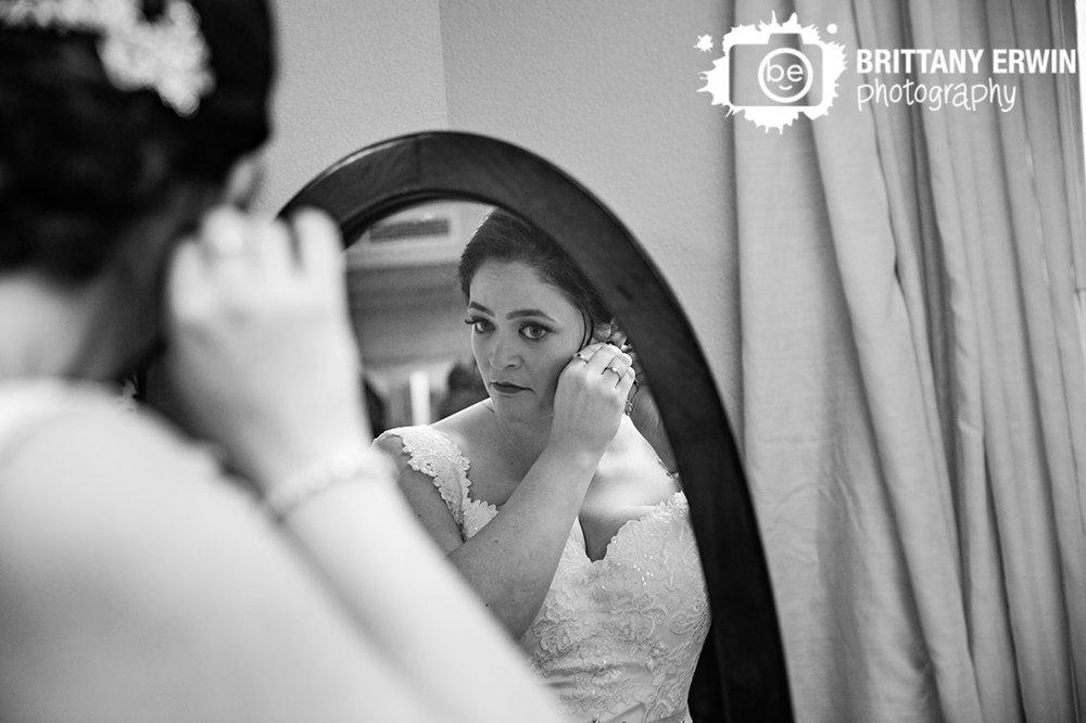 Bride-getting-ready-in-mirror-putting-on-earrings.jpg