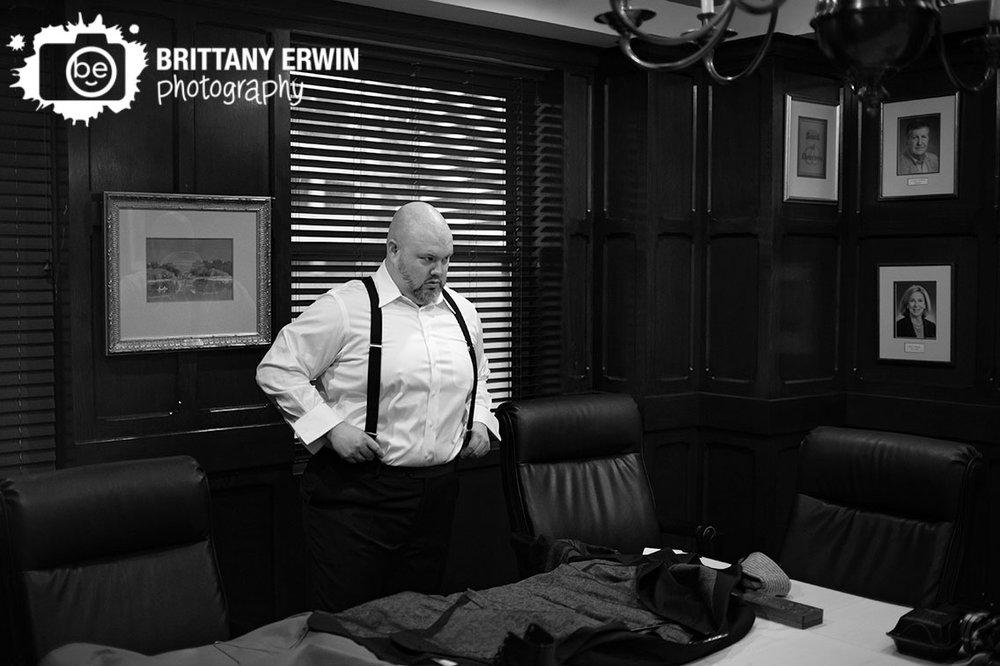 groom-getting-ready-in-a-board-room-putting-on-suspenders.jpg