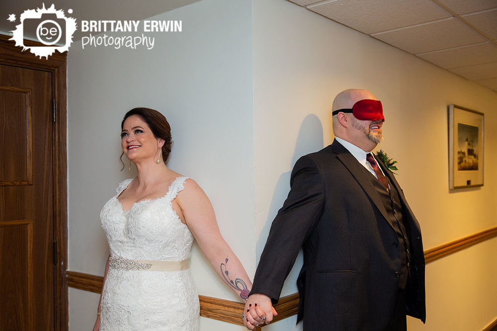 groom-blindfolded-couple-holding-hands-around-a-corner-before-the-ceremony.jpg