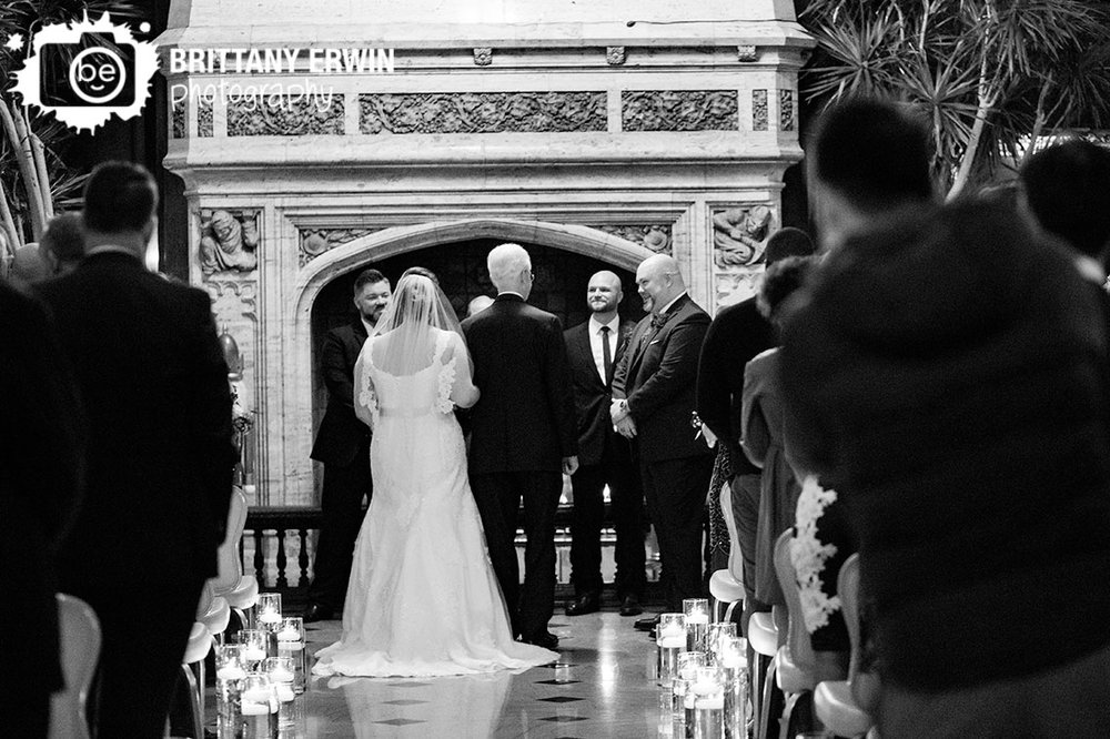 bride-walking-down-the-aisle-with-father-groom-reaction-at-fireplace.jpg