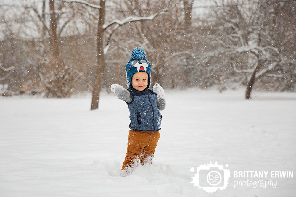Toddler-boy-playing-in-the-snow-with-walrus-hat-throwing-fluffy-snowballs.jpg