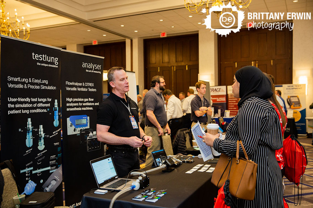 Indianapolis-event-photographer-attendees-interacting-at-booth-Indiana-Biomedical-Society-conference.jpg