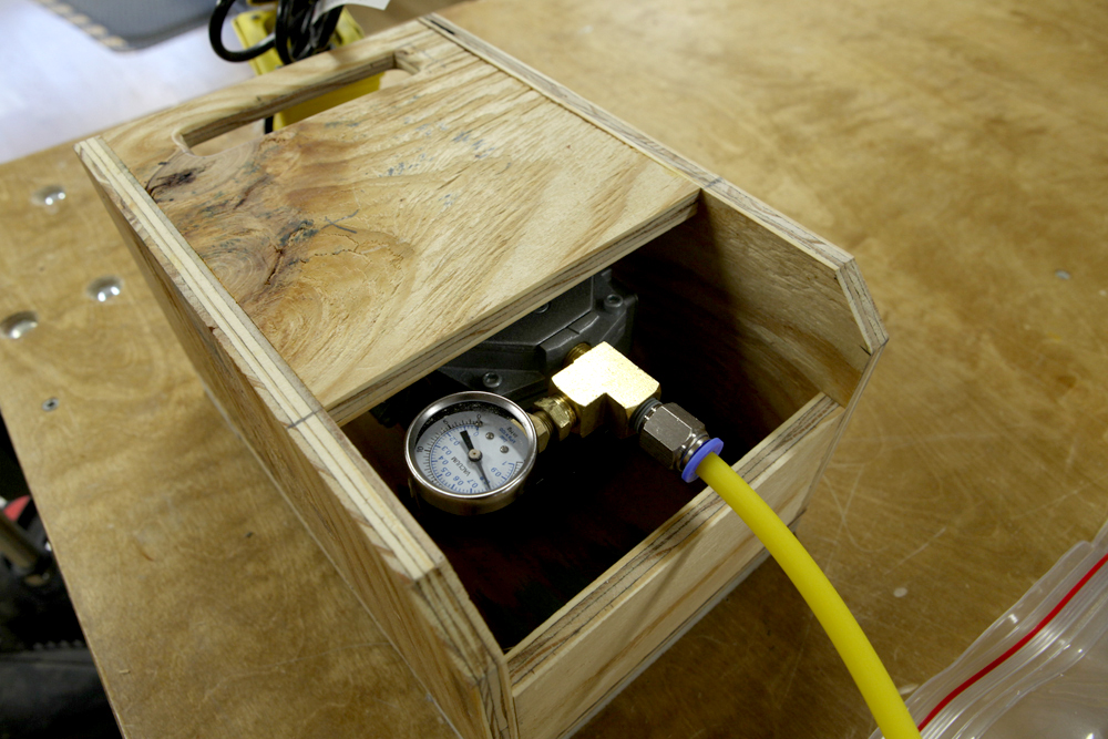The vacuum pump inside the protective box.