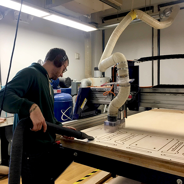 Second-year  Products of Design  student Kevin Cook cuts a desk organizer out of plywood using the CNC.