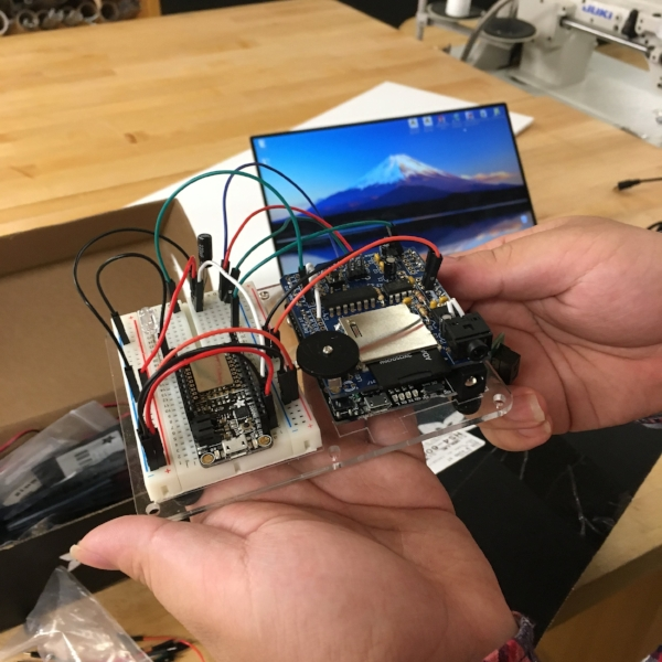 First-year  MFA Products of Design  student Hui Zheng, is putting the finishing touches on the wiring for an Arduino plus sound board combination.