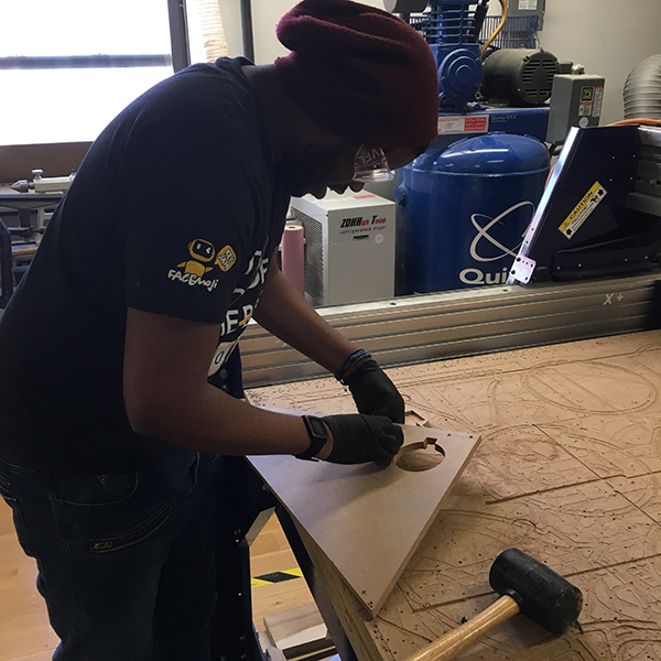 First-year  MFA Interactive Design  student Kenrick Ramsay is cleaning MDF parts, recently cut with the Visible Futures Lab's ShopBot CNC Router.