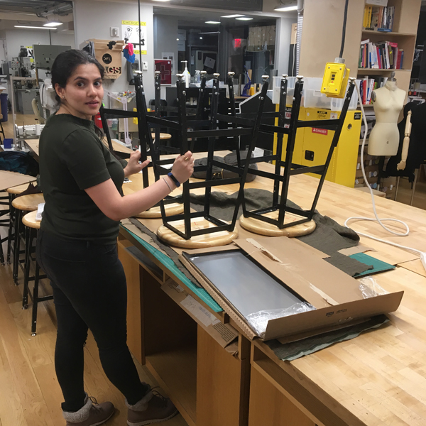 First-year  MFA Design  student Nillu Rathod is laminating woolen plain-weave textile to cardboard and weighing down the parts with some of the Visible Futures Lab's heavy stools, one of the more easily overlooked tasks in object building.