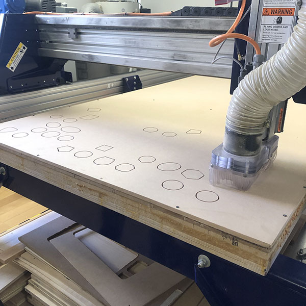 Our very own student worker Owen Keogh is in the VFL today to use the CNC router. He's currently helping an artist produce a series of picture frames that are in the shape of space program patches. MDF