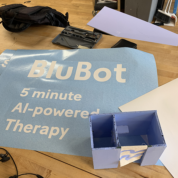 Evie is using the vinyl plotter to cut some text for her signage. Her project is centered around a learning AI Therapist that will engage with the public by asking questions about the human condition.