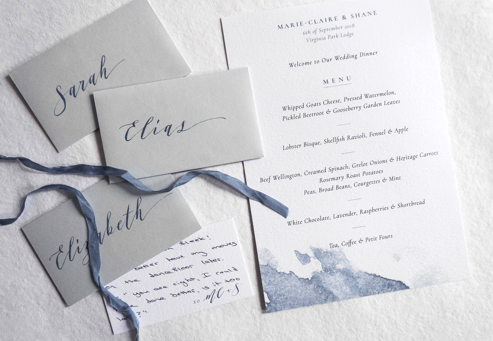 Menu with dusty blue watercolor wash. Calligraphy placenames in tiny envelopes with handwritten notes for each guest…this couple really thought about the little details.