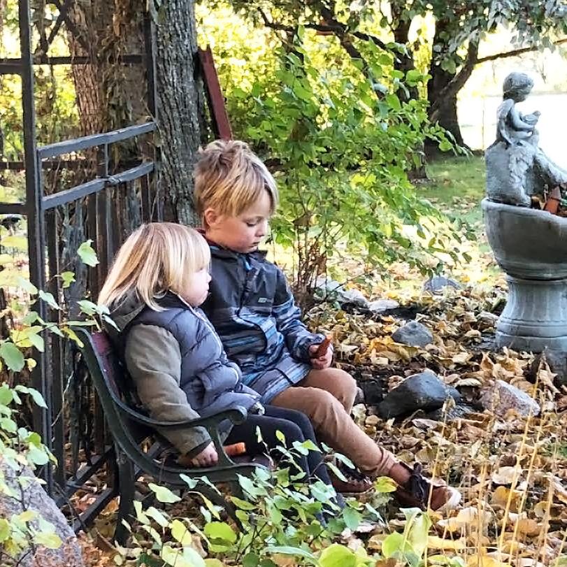 sister and brother sitting garden portage la prairie manitoba