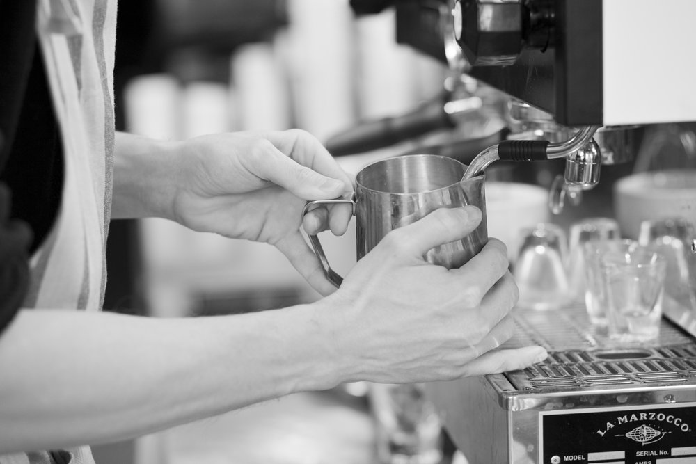A barista steaming milk at an espresso machine