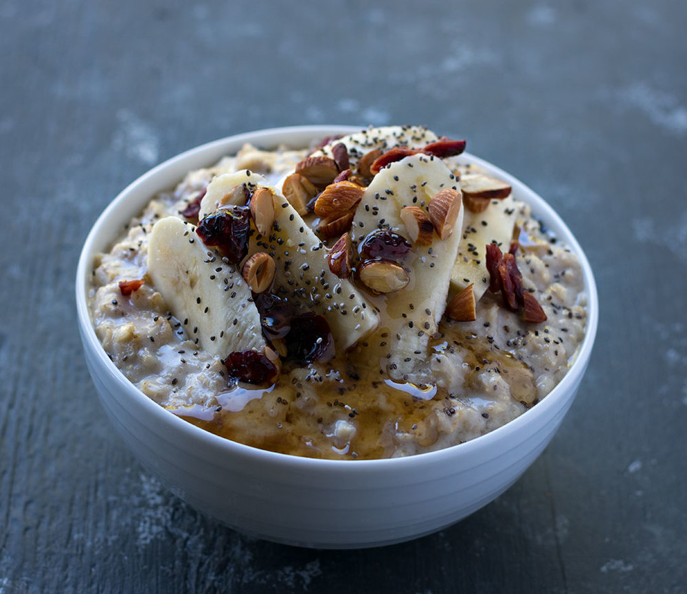 Slow-Cooked Sunday Morning Oats with Cranberries, Banana, Toasted Almonds, Chia Seeds and Maple Syrup