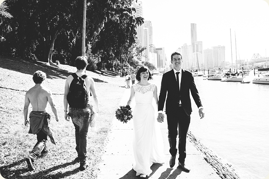 Short dude with no shirt on, some other dude with a back pack and no shirt with bride and groom in the Brisbane City Botanic Gardens