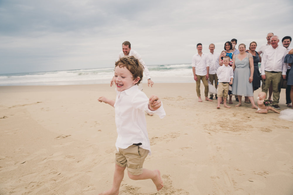 Child running out of group photo at wedding
