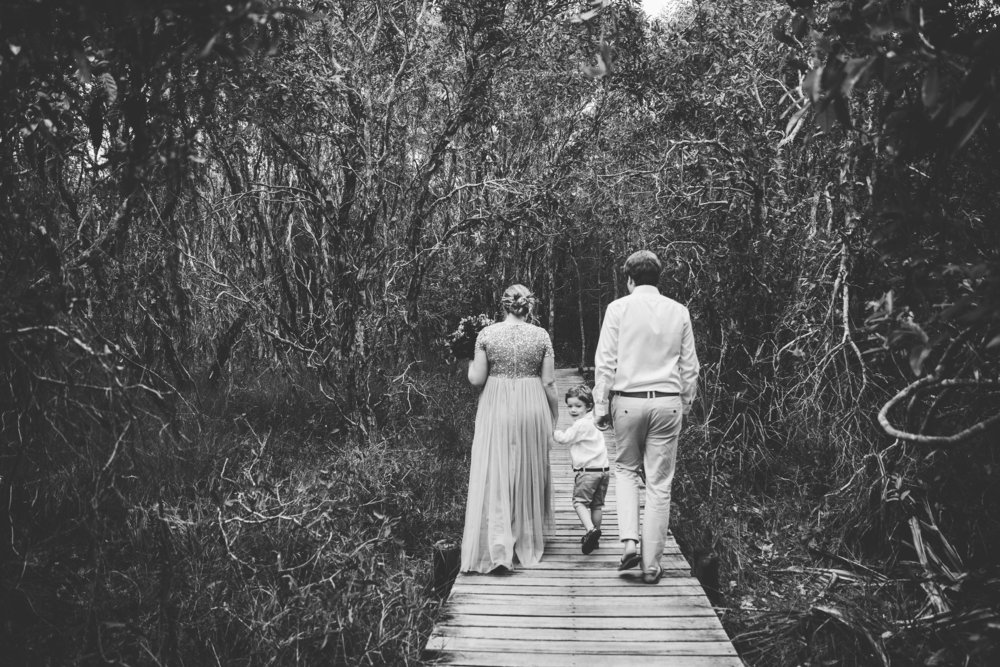 bride, groom and child walking down path