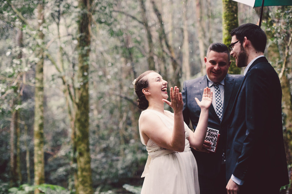 bride laughing while it rains during elopement
