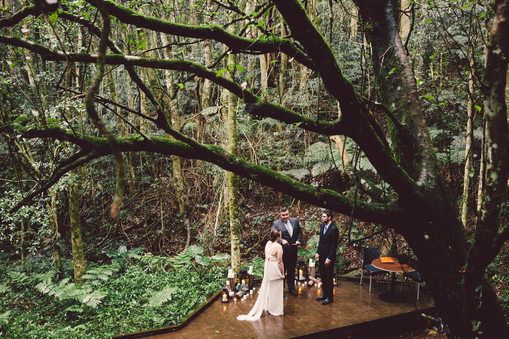 bride and groom eloping surrounded by candles in rainforest