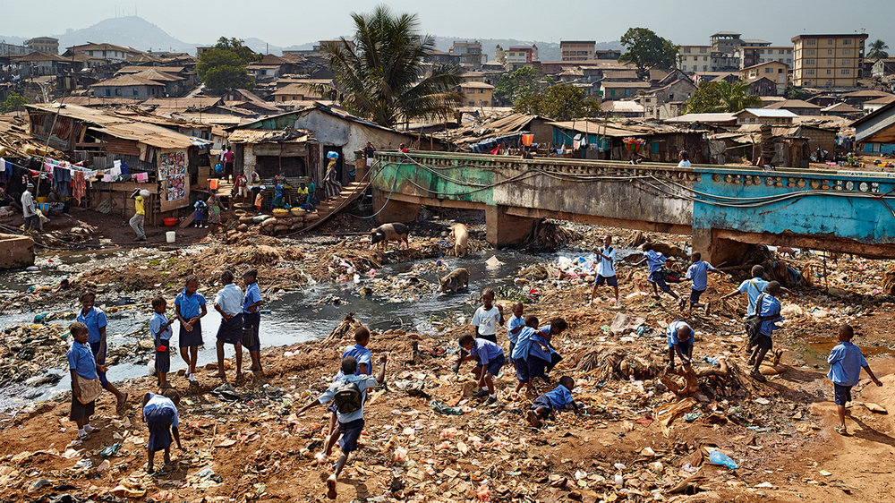 Students in central Freetown playing in trash piles out side their school: Kroo Bay Community Primary School