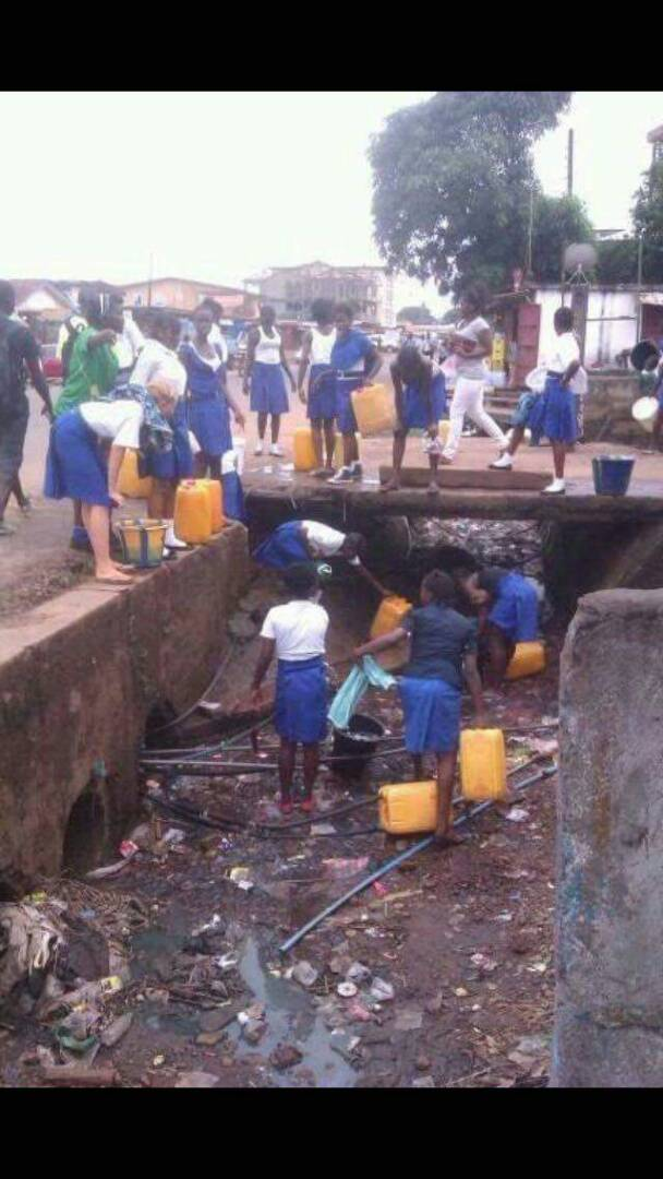 Students fetching water in gutters due to water crisis in Sierra Leone, West Africa