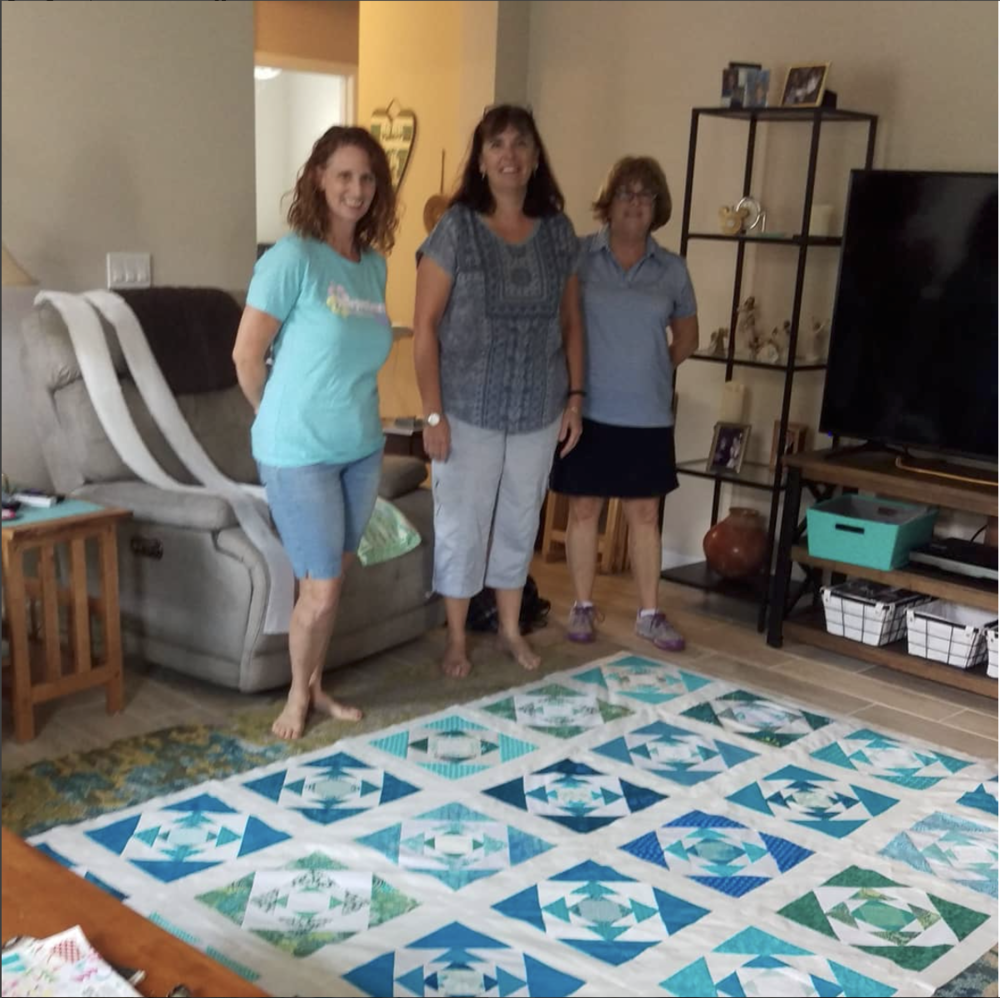 Our group's collaborative quilt shown with Diana, Ede, and Kathy